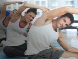 Men and women doing a side stretch in a class